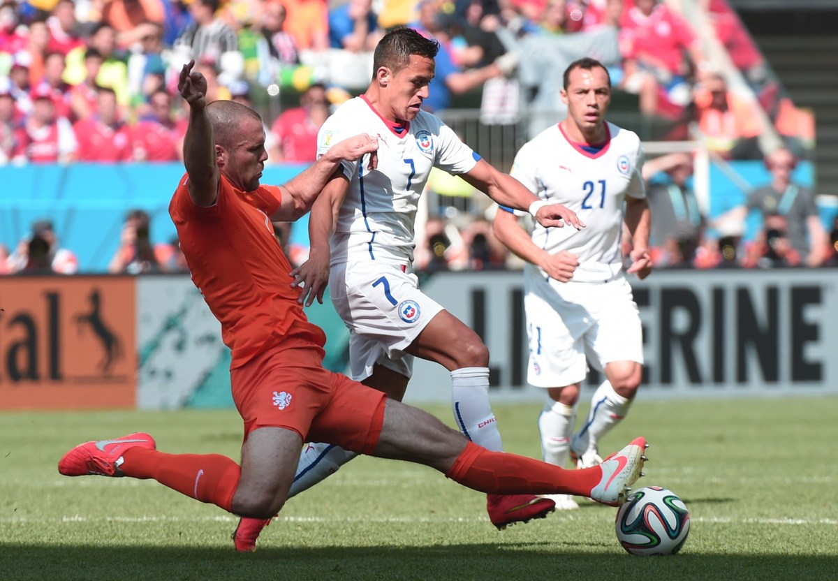 Netherlands' defender Ron Vlaar (L) and Chile's forward Alexis Sanchez vie during the Group B football match between Netherla
