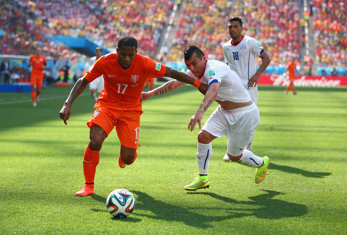 SAO PAULO, BRAZIL - JUNE 23:  Jeremain Lens of the Netherlands and Gary Medel of Chile compete for the ball  during the 2014