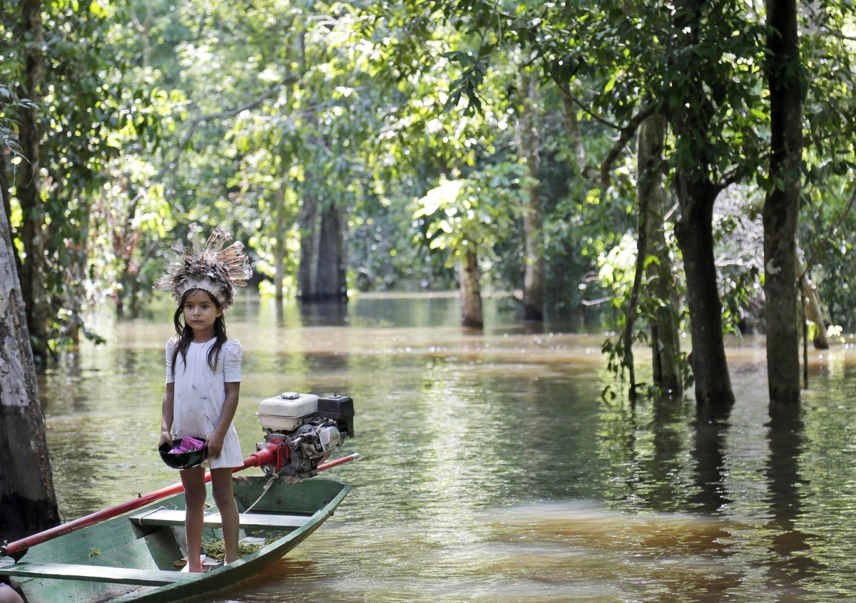 A young girl waits for visitors on a small boat on the Amazon River during the 2014 soccer World Cup near Manaus, Brazil, on