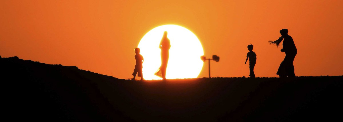 A Bahraini family is seen as the sun sets on a rocky ridge in the Sakhir desert area, Bahrain on November 7, 2009. (Hasan Jam
