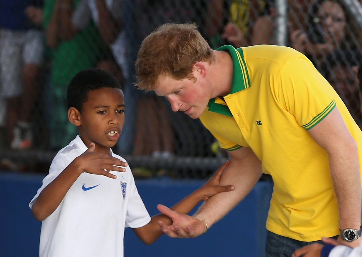 SAO PAULO, BRAZIL - JUNE 25:  Prince Harry plays football as he visits the ACER Charity for disadvantaged children on June 25