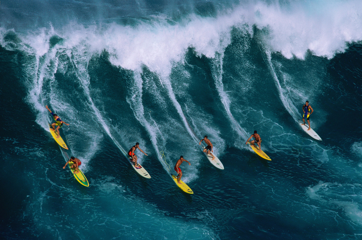 Seven surfers ride a large wave at Waimea on Oahu. The bay at Waimea is home to Hawaii's biggest surf with waves reaching up