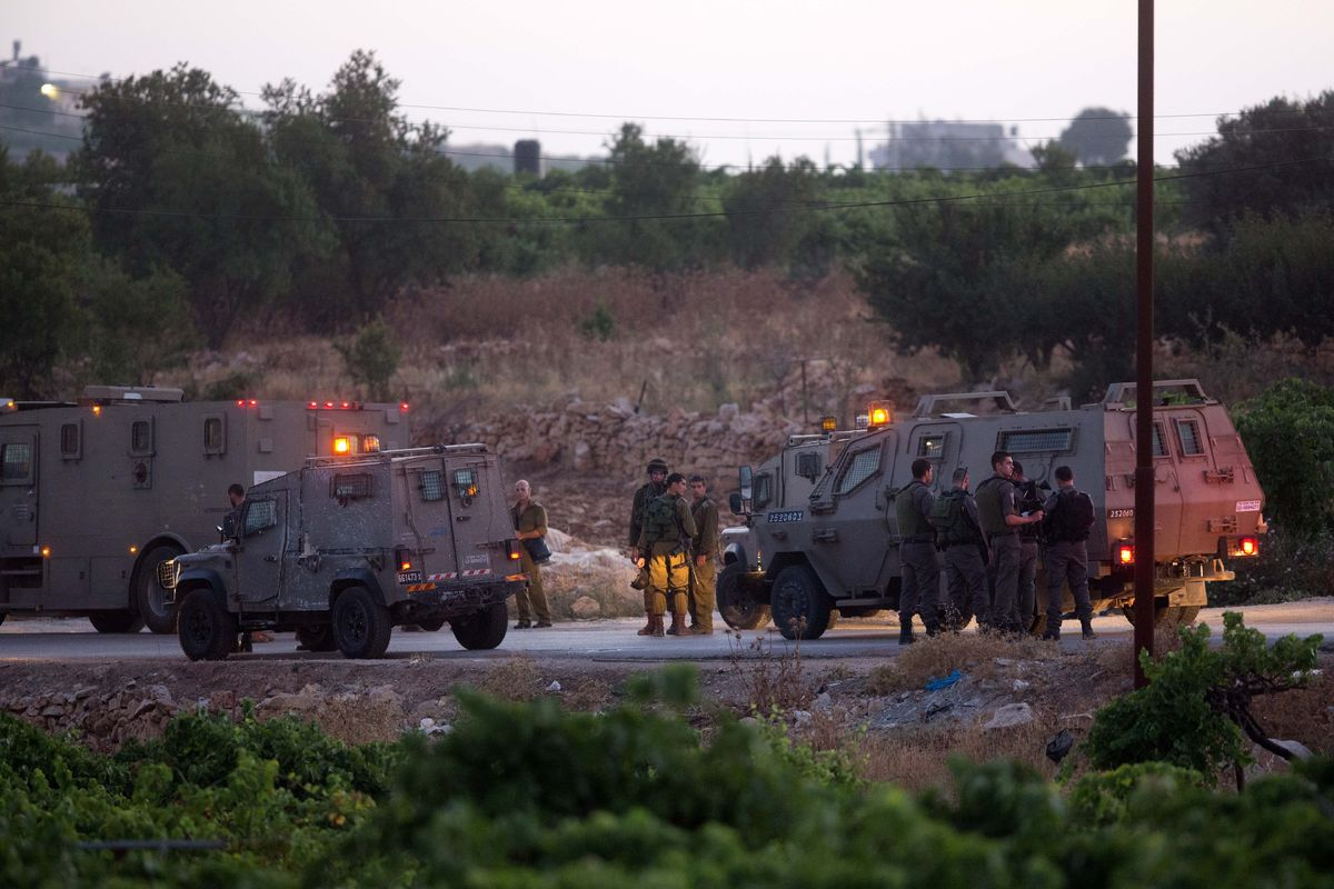 Israeli soldiers stand next to their vehicles on June 30, 2014 in the village of Halhul, near the West Bank town of Hebron, w