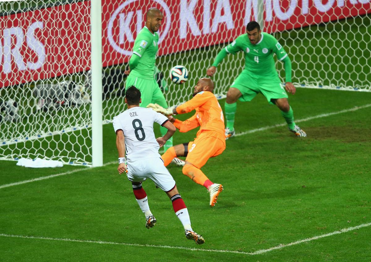 PORTO ALEGRE, BRAZIL - JUNE 30: Mesut Oezil of Germany scores his team's second goal past Rais M'Bolhi of Algeria during the