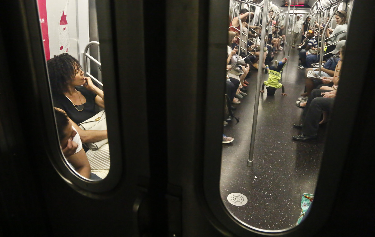 In this June 17, 2014 photo, subway riders are treated to a performance of acrobatic dancers from the dance troupe W.A.F.F.L.