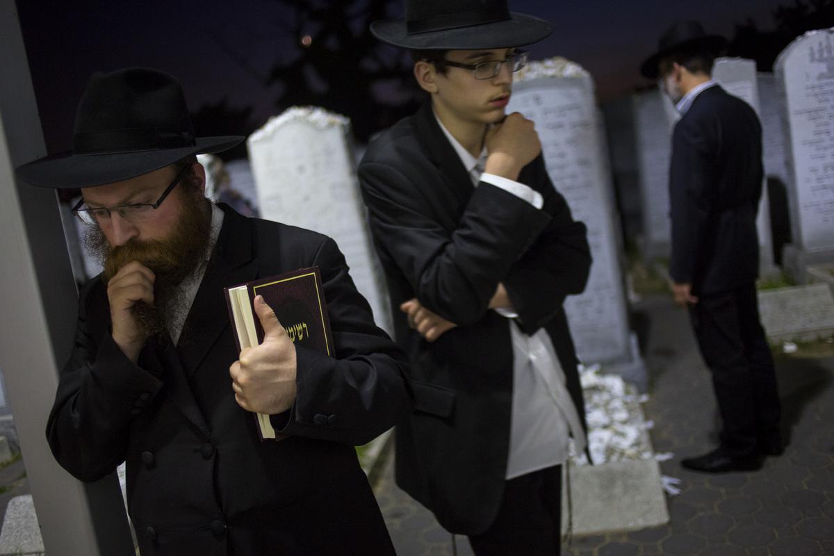 Visitors pray at the gravesite of the Lubavitcher Rebbe, Rabbi Menachem Mendel Schneerson June 30, 2014 at the Old Montefiore