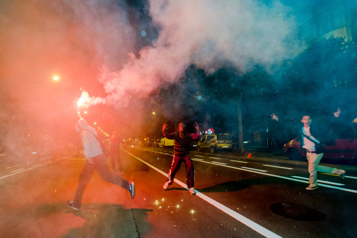 Fans of the Belgian national soccer team celebrate as they run on a main boulevard after Belgium won the World Cup round of 1