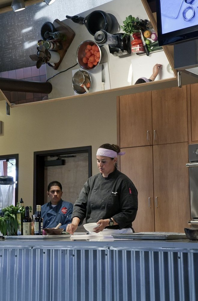 """Chef Michelle """"Mica"""" Roetzer, ably assisted by Angel Valadez, instructs students of the Santa Fe School of Cooking and regale"""