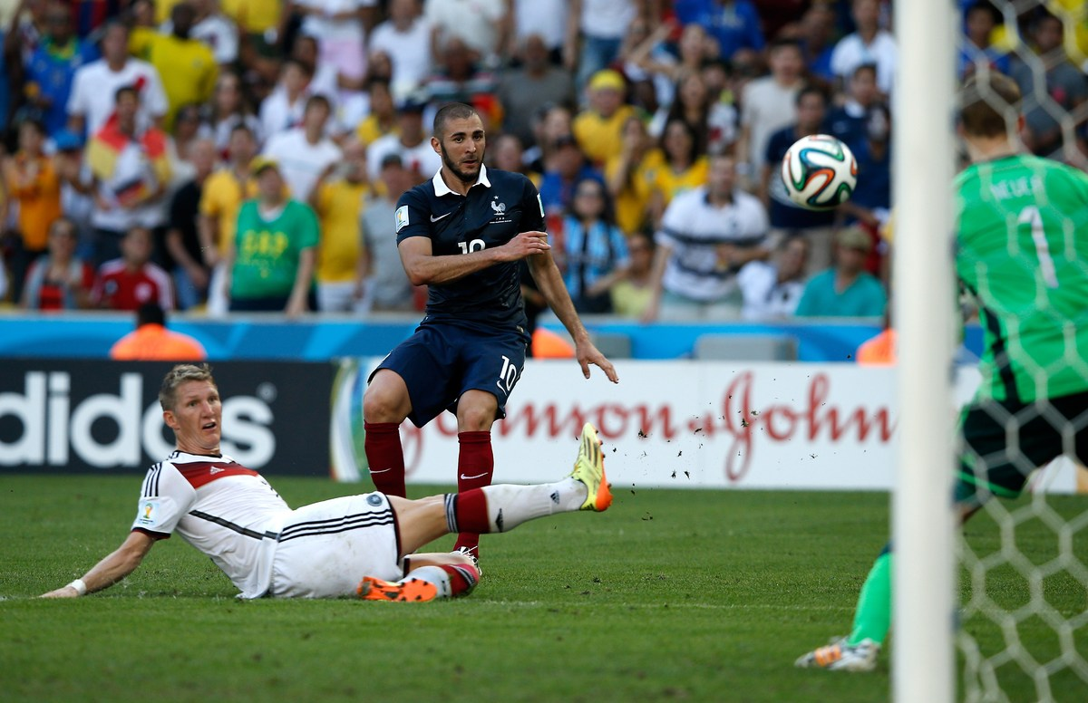 France's forward Karim Benzema (C) takes a shot on goal as Germany's midfielder Bastian Schweinsteiger watches on during the
