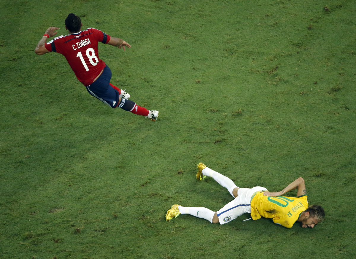Brazil's Neymar grimaces in pain during the World Cup quarterfinal soccer match between Brazil and Colombia at the Arena Cast