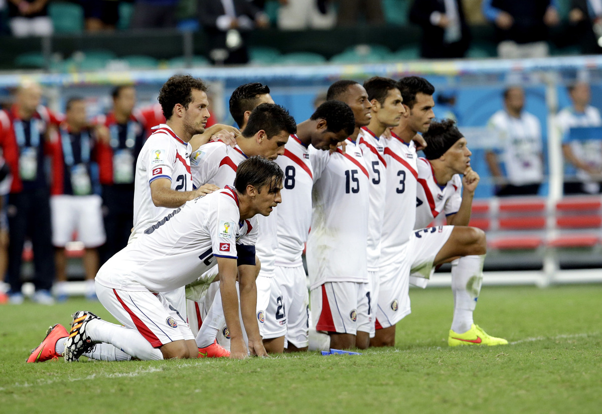 Costa Rica players watch penalty kicks on their knees during the World Cup quarterfinal soccer match between the Netherlands