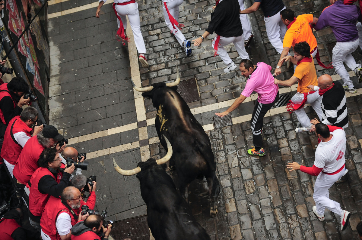 Revelers run ahead ''Victoriano del Rio Cortes'' fighting bulls on Estafeta corner during the running of the bulls at the San