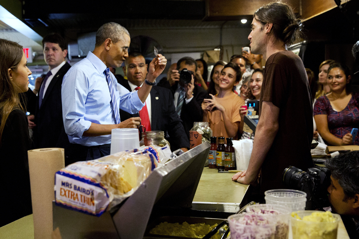 President Barack Obama scrutinizes his credit card as he jokes with the wait staff while ordering barbecue at Franklin Barbec