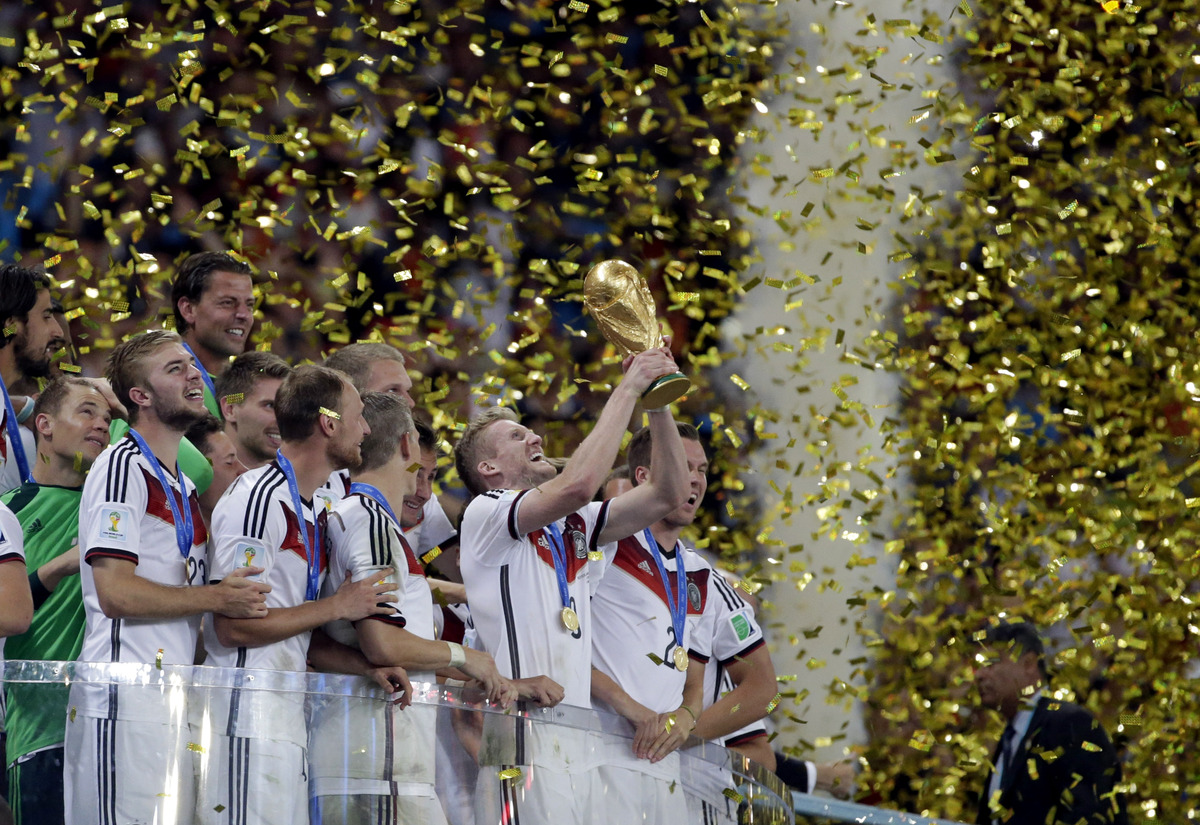 Germany's Andre Schuerrle holds up the World Cup trophy as the team celebrates their 1-0 victor over Argentina after the Worl