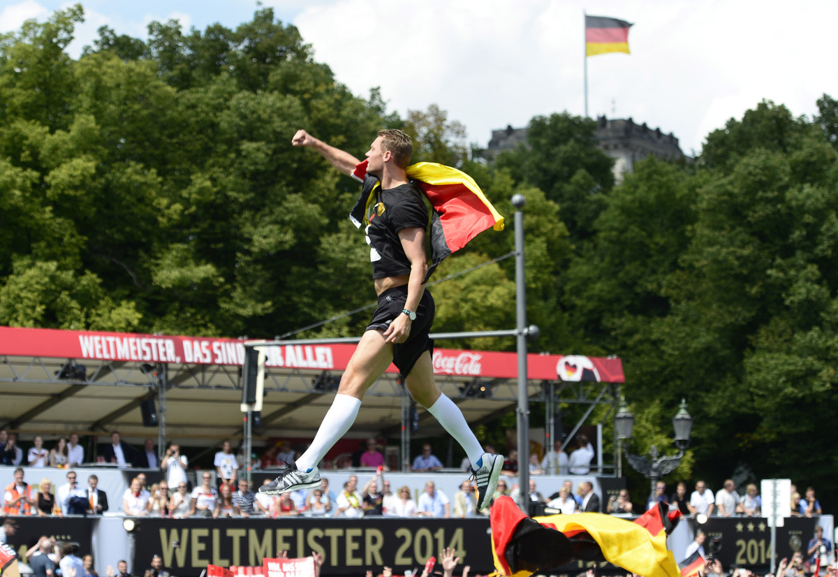Goalkeeper Manuel Neuer is airborne during a fan party after the arrival of the German national soccer team in Berlin Tuesday