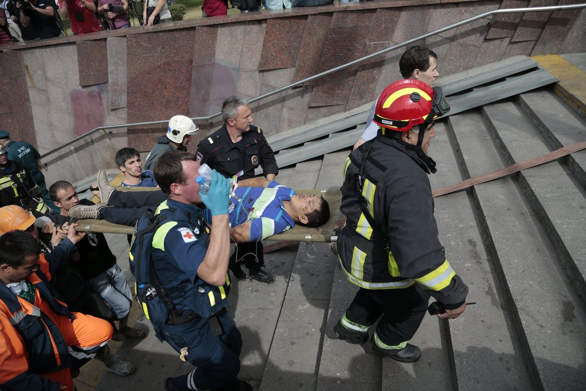 Paramedics, a police officer and a volunteer carry an injured man out from a subway station after a rush-hour subway train de