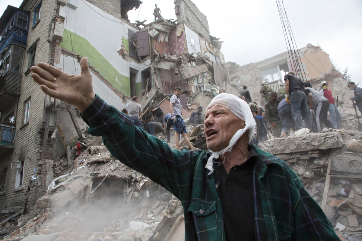 Igor Chernetsov, whose wife was killed in a building demolished by an airstrike, gestures near the collapsed structure in Sni
