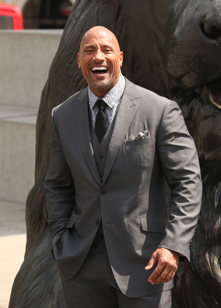 Dwayne Johnson poses in front of one of the lion statues by Nelson's column on Trafalgar Square in central London, during a p