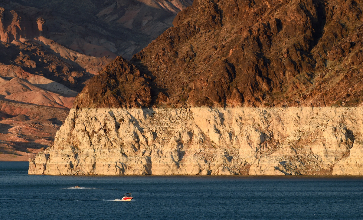 "Boaters near Horsepower Cove pass in front of a white ""bathtub ring"" on the rocks on July 13, 2014 in the Lake Mead National"