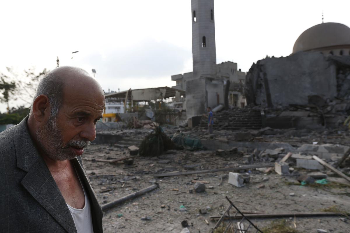Palestinian Khaled Sharmi, 67, walks past the Al Aqsa Martyrs mosque, destroyed by an overnight Israeli strike, in Gaza City