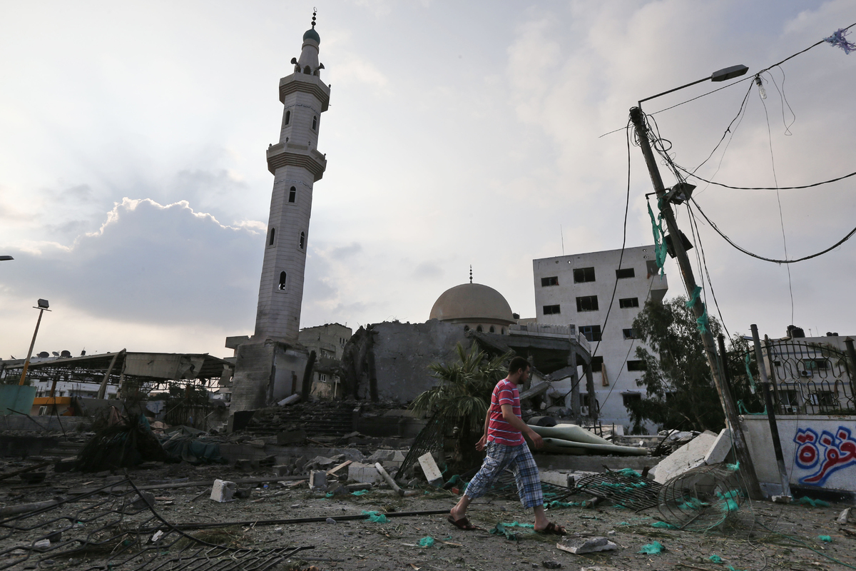 A Palestinian man walks past the Al Aqsa Martyrs mosque, destroyed by an overnight Israeli strike, in Gaza City, Tuesday, Jul
