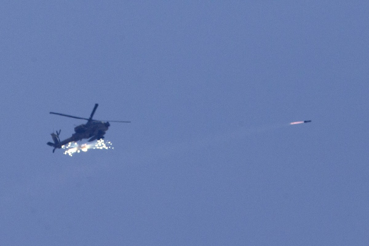 An Israeli Apache attack helicopter fires a missile over the Gaza Strip as seen from Israel's border with Gaza, on July 22, 2