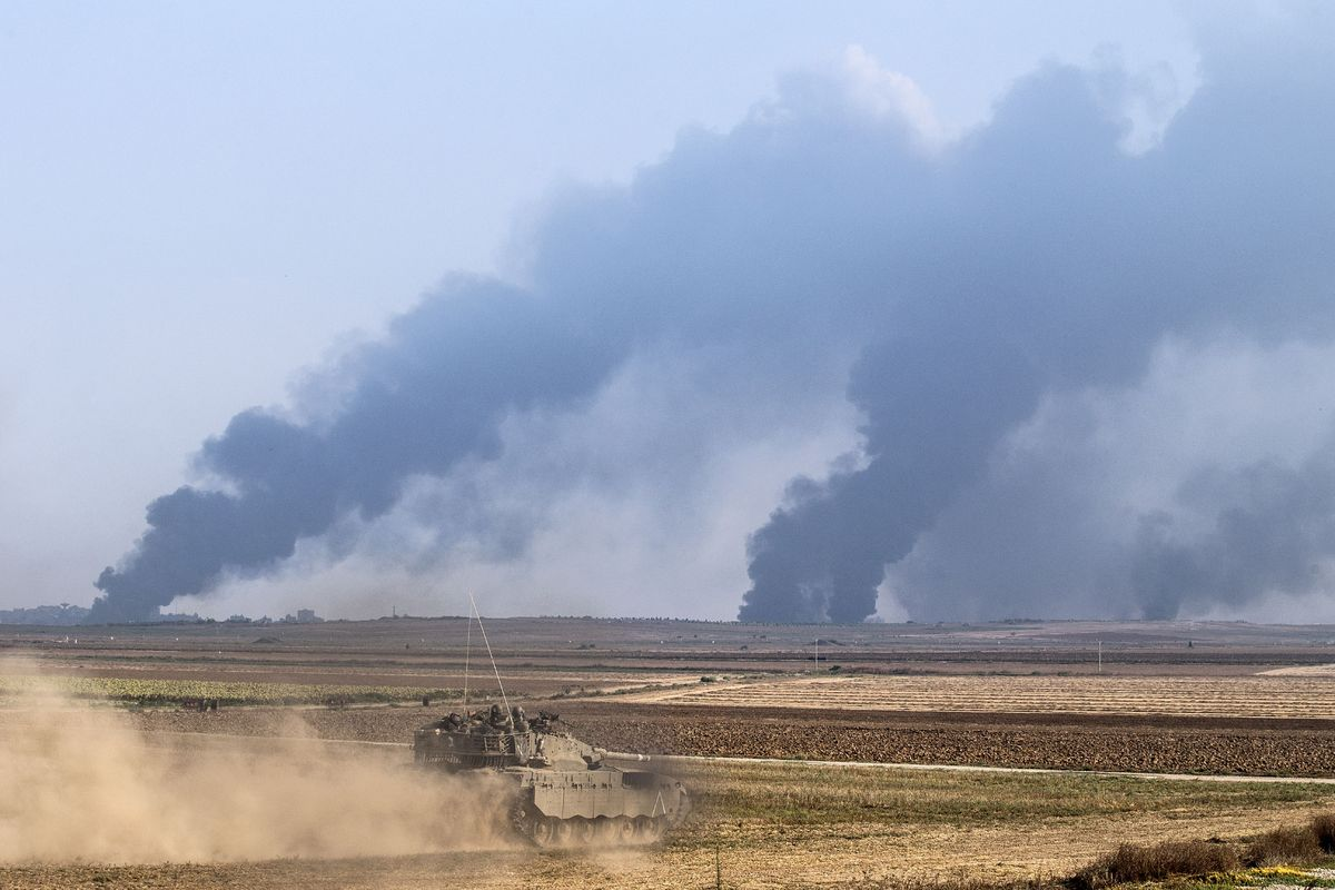 An Israeli Merkava tank rolls on the Israeli side of the border with the Gaza Strip, on July 22 , 2014, as smoke billows from