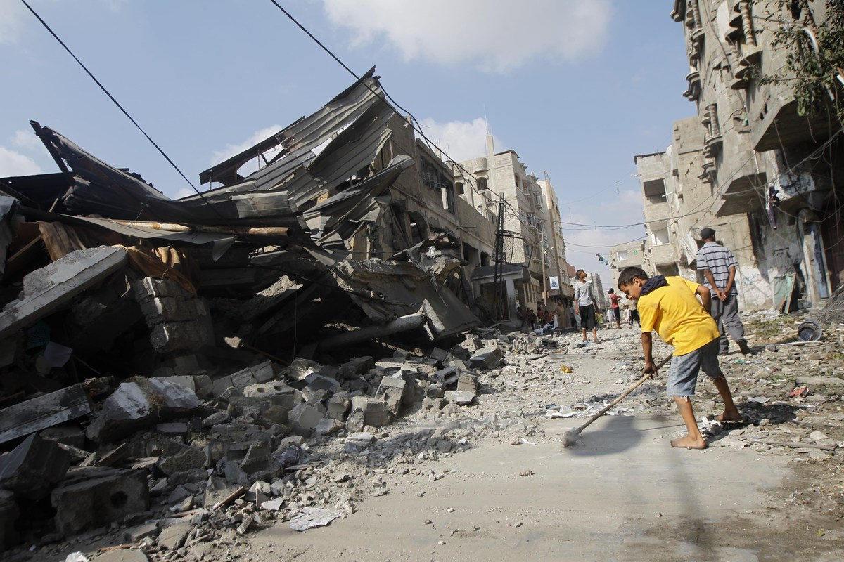 A Palestinian boy sweeps the ground outside a destroyed mosque,  following an overnight Israeli military strike, on July 22,