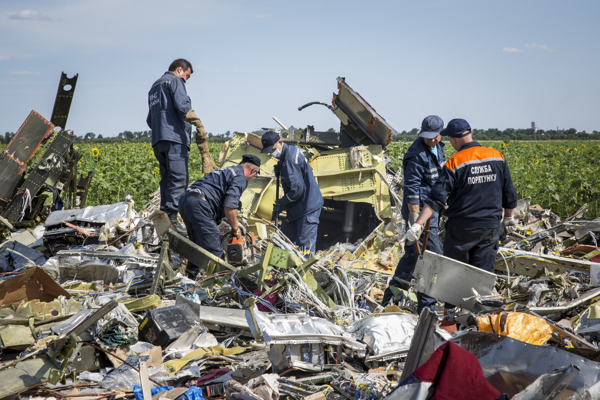 RASSIPNOYE, UKRAINE - JULY 20:  Ukrainian rescue servicemen inspect part of the wreckage of Malaysia Airlines flight MH17 on
