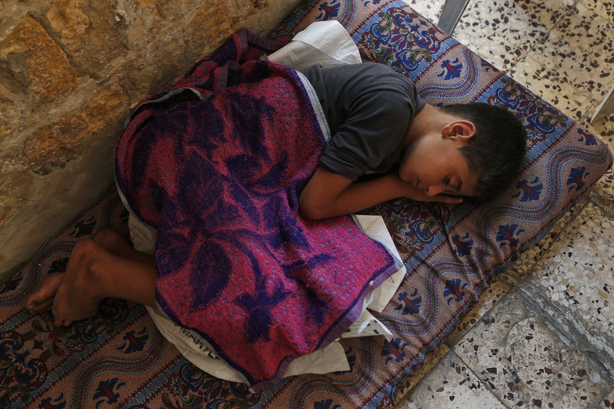 A Palestinians boy sleeps on a mattress on the floor of the grounds of the St. Porphyrios Church in Gaza City, on Wednesday,