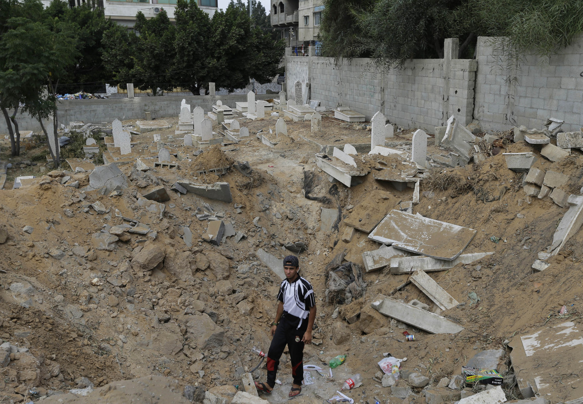 A Palestinian looks for human remains by graves destroyed from an Israeli missile strike, in a crater caused by the strike, a
