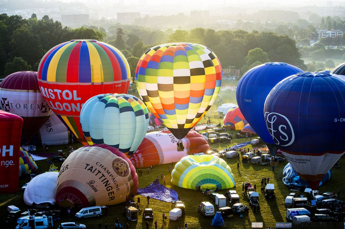 Hot air balloons are inflated ahead of a mass ascent at the 36th International Balloon Fiesta at the Ashton Court Estate near