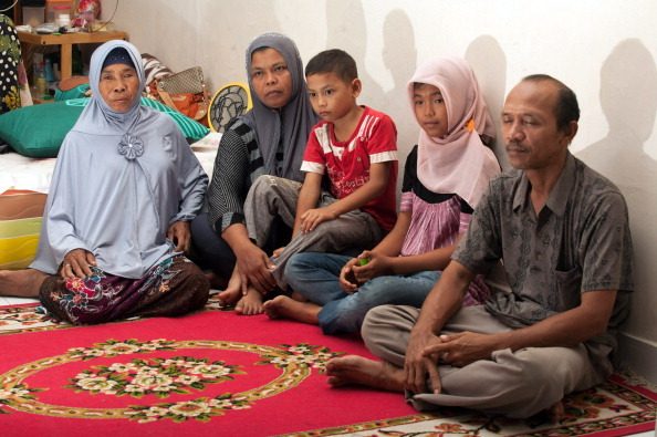 Missing Indonesian tsunami victim Raudhatul Jannah (2nd R), aged 14, sits with mother, Jamaliah (2nd L), holding youngest son