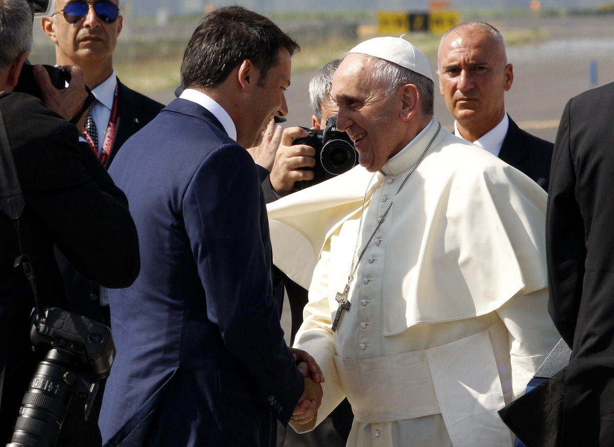 Pope Francis is greeted by Italian Premier Matteo Renzi, left, as he arrives to board a plane to South Korea, at Rome's Fiumi