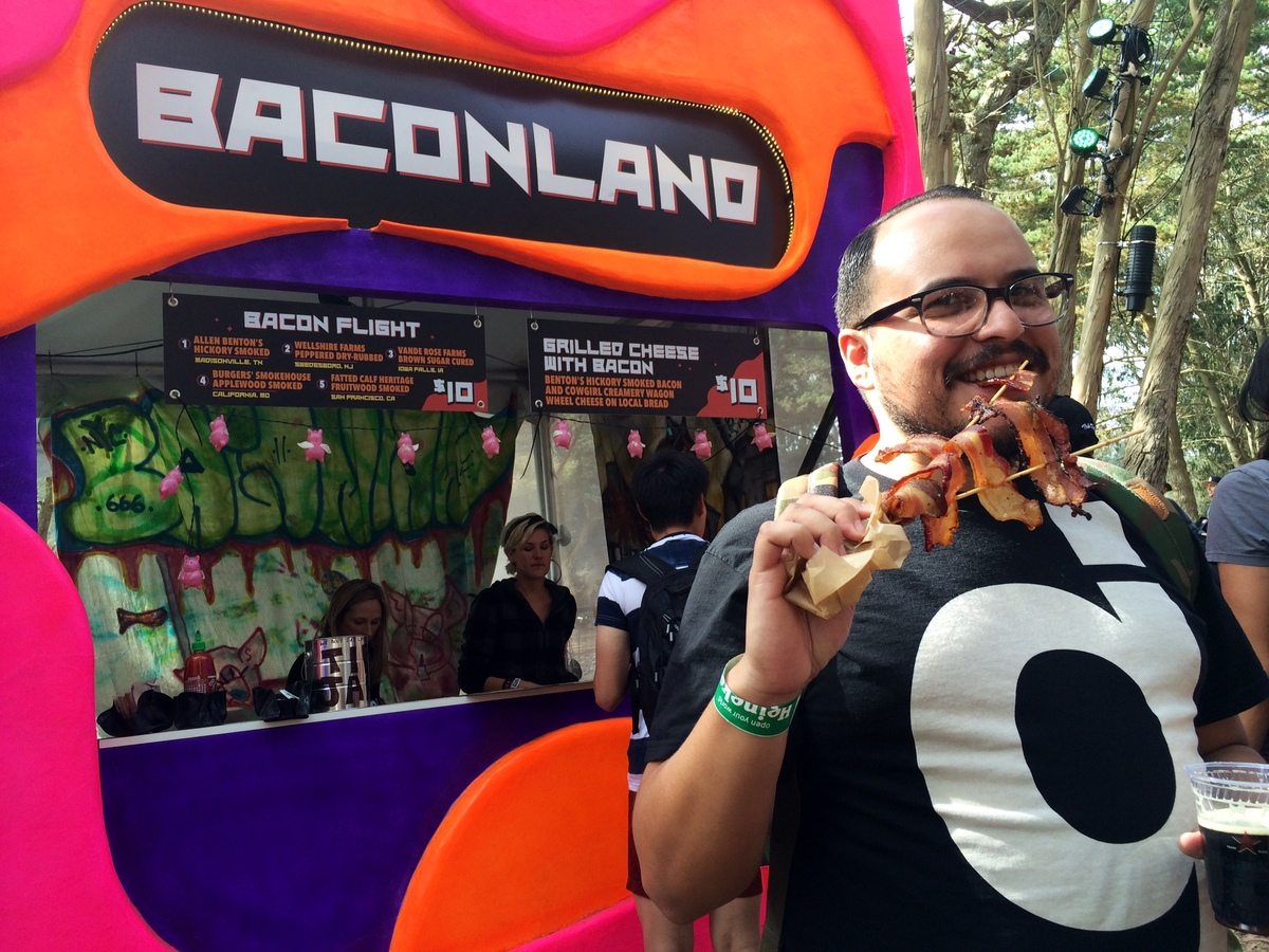 A festival-goer enjoys a flight of 5 different types of bacon at the new Outside Lands vendor Baconland. After seeing so many
