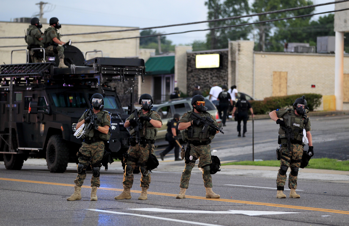 Police wearing riot gear try to disperse a crowd Monday, Aug. 11, 2014, in Ferguson, Mo. The FBI opened an investigation Mond