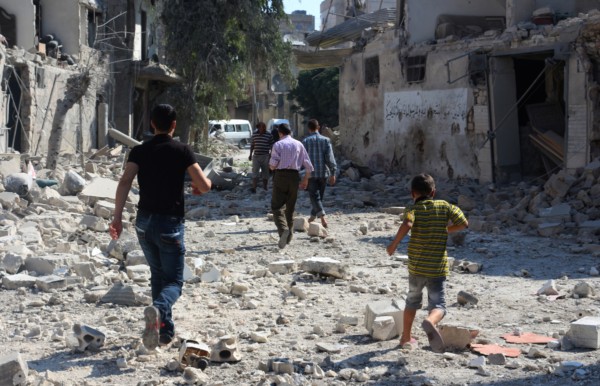 Syrians walk around the wreckage of buildings after a reported barrel bomb strike from regime forces on the Maadi neighborhoo