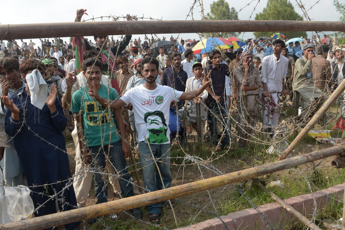 Supporters of Pakistani opposition politician Imran Khan stand behind barbed wire during an anti-government march in Islamaba