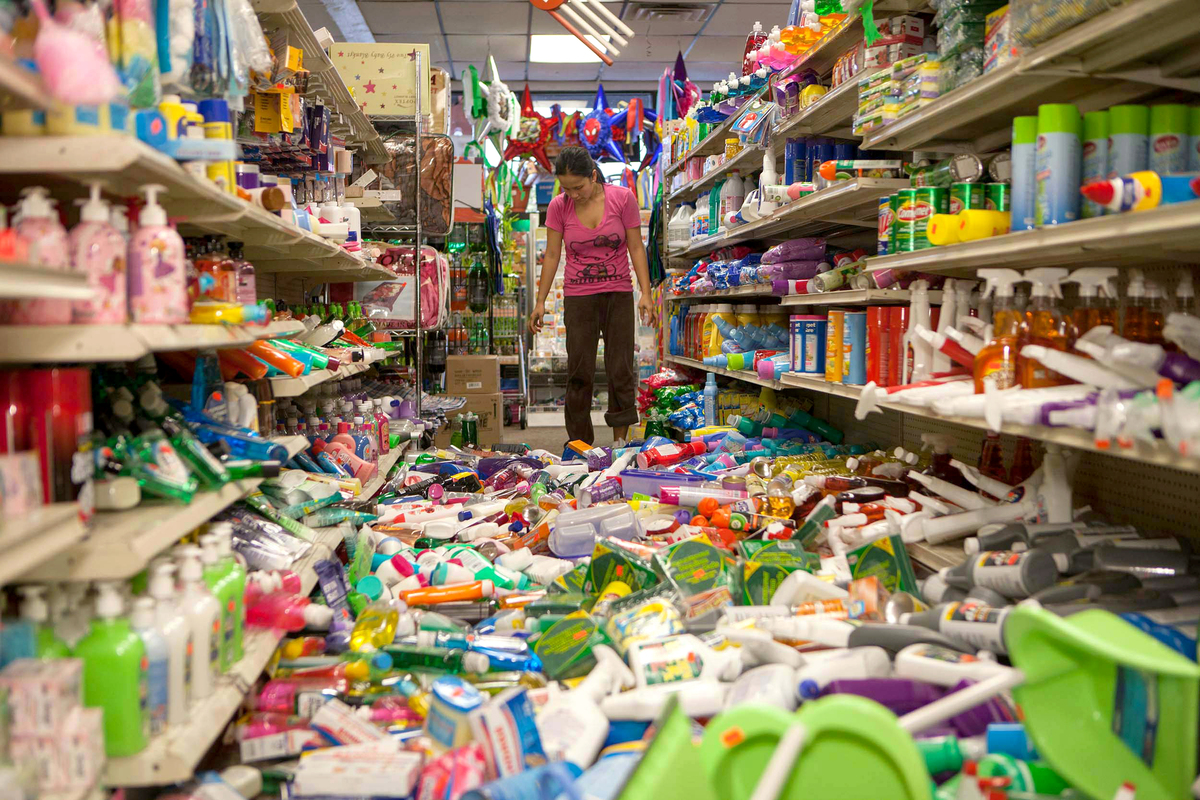 Nina Quidit cleans up the Dollar Plus and Party Supplies Store in American Canyon Calif. after an earthquake on Sunday Aug. 2