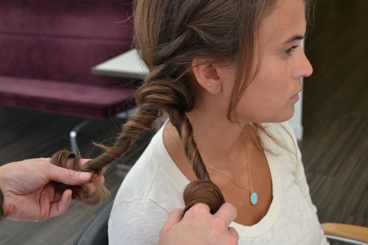 Spray texturizing spray again on hair below the bobby pins to create fullness. Then make two twists with this remaining hair