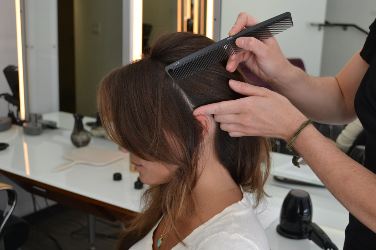Gather hair to one side, while leaving a few front pieces of hair out to frame the face. Curl these pieces with a 1-inch barr