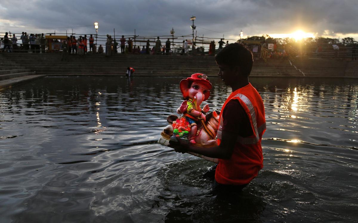 A volunteer prepares to immerse a clay idol of elephant-headed Hindu god Ganesha on the first day of Ganesh Chaturthi festiva