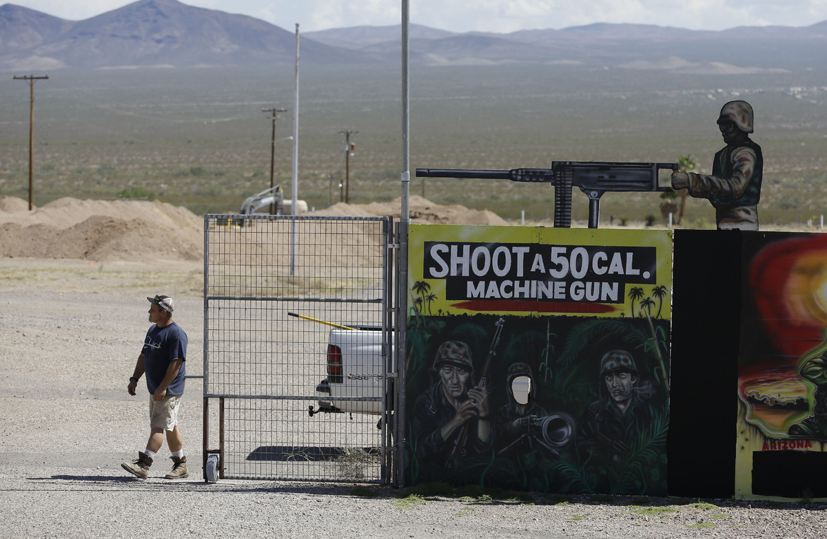 A man closes off an entrance to the Last Stop outdoor shooting range Wednesday, Aug. 27, 2014, in White Hills, Ariz. Gun rang