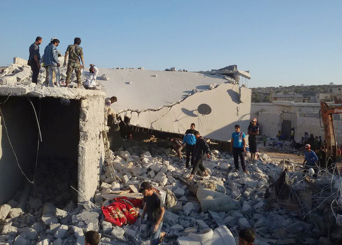 Syrians look at a damaged house in the village of Kfar Derian, which according to opposition activist group Edlib News Networ