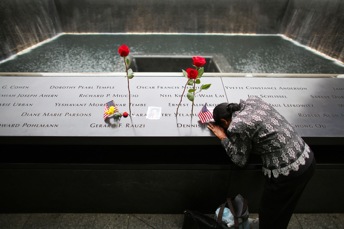 NEW YORK, NY - SEPTEMBER 11: A woman grieves at her husband's memorial at South Tower Reflecting Pool before the memorial obs