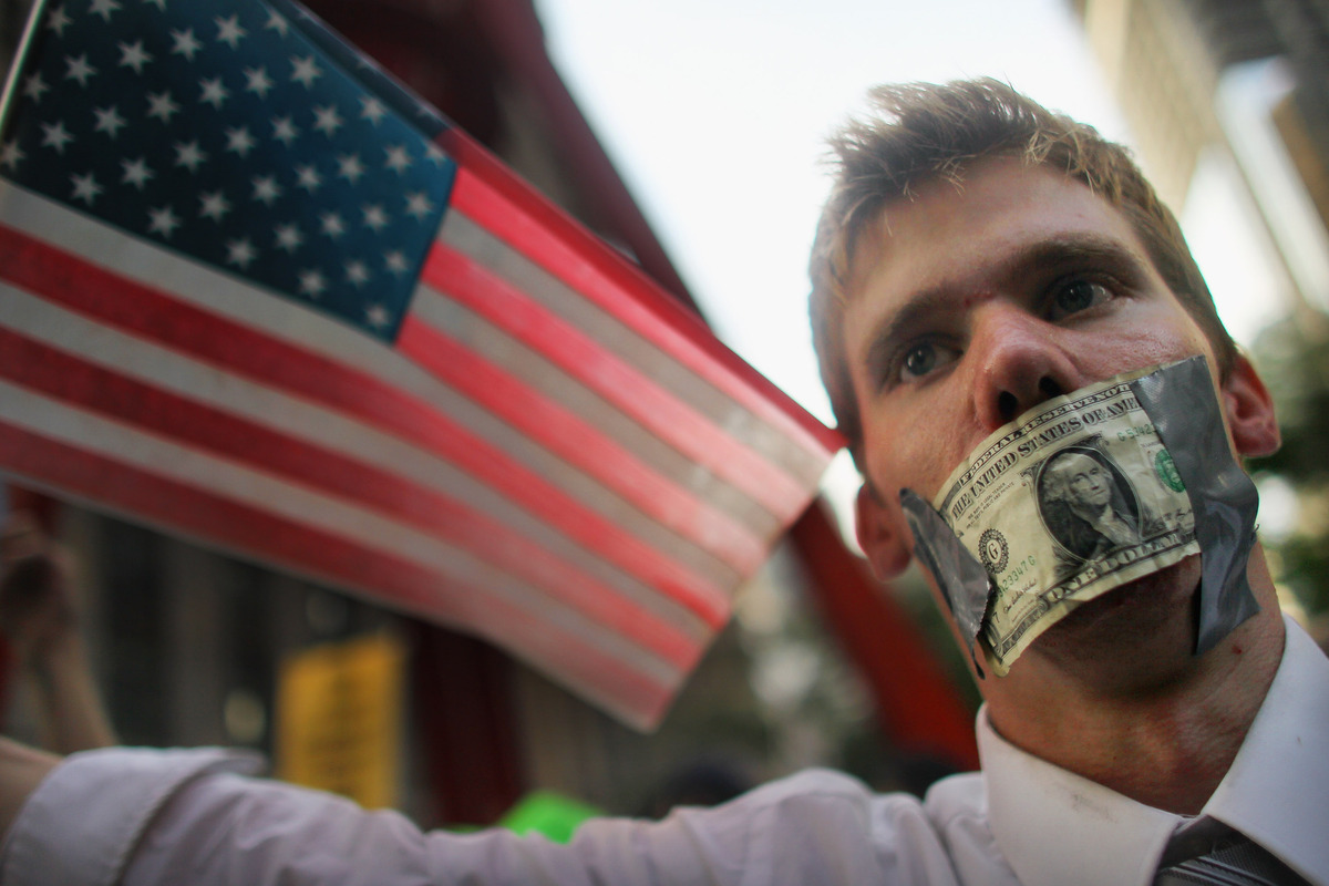 A protester wears a dollar bill over his mouth at the start of a march by demonstrators opposed to corporate profits on Wall