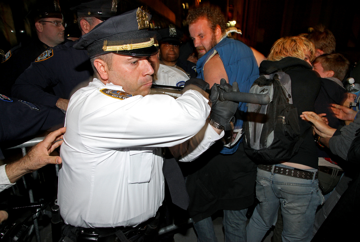A New York City police lieutenant swings his baton as he and other police try to stop protesters who breached a barricade to