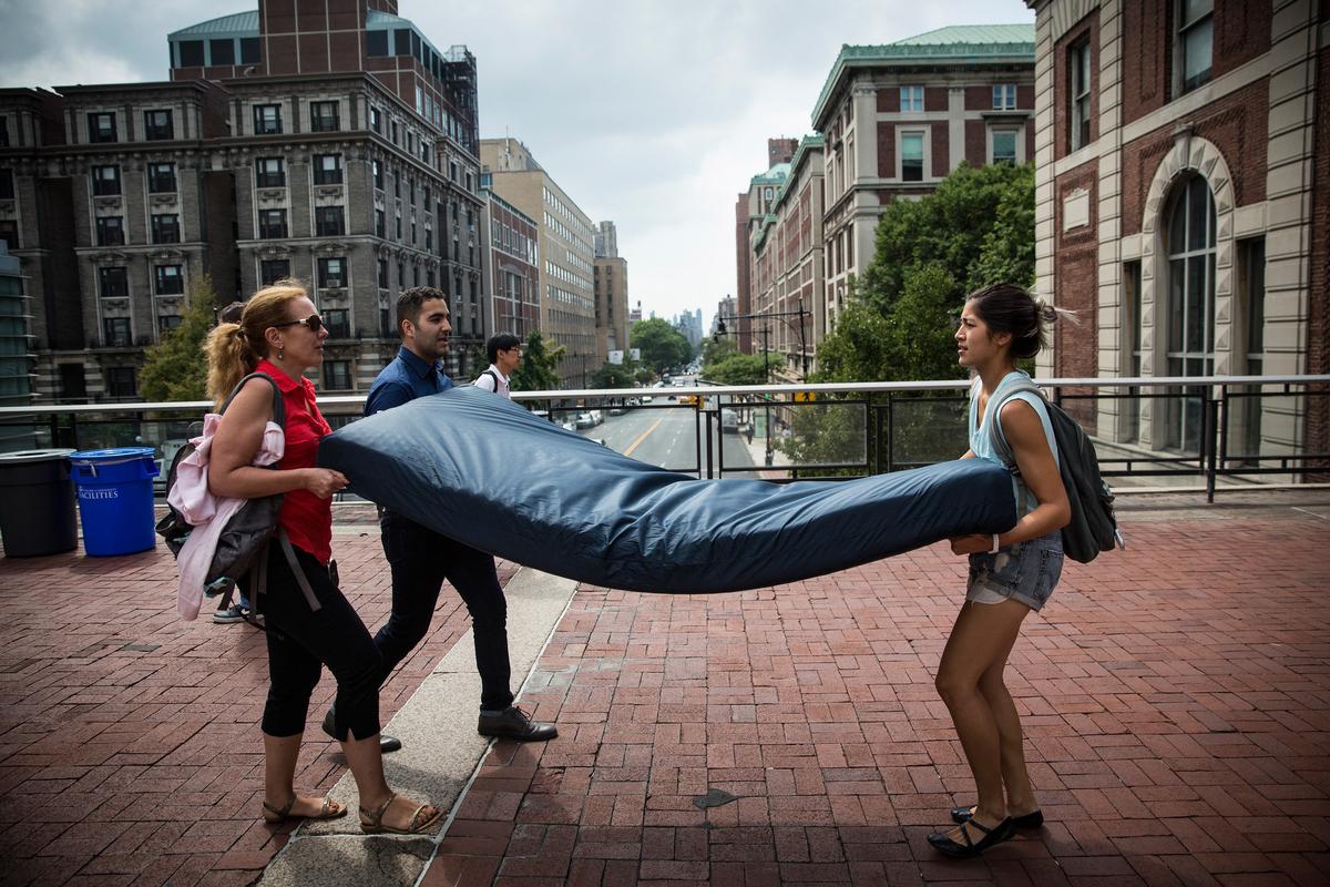 NEW YORK, NY - SEPTEMBER 05:  Emma Sulkowicz (R),  a senior visual arts student at Columbia University, carries a mattress, w
