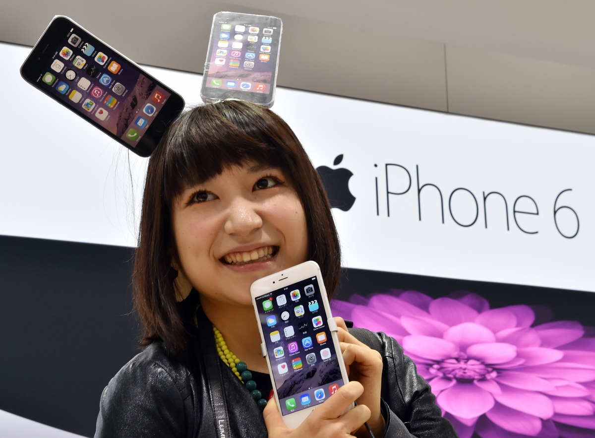 An Apple gadget fan displays Apple's newest smartphone iPhone 6 Plus asafter buying it at Softbank's mobile phone shop in Tok
