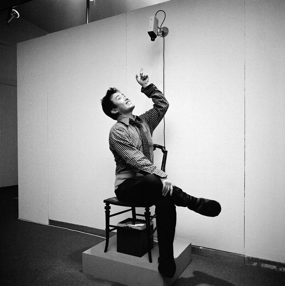 "Paik sitting in TV Chair (1968/1976) in ""Nam June Paik Werke, 1946–1976: Music, Fluxus, Video,"" 1976.  Photo credit: © Friedr"